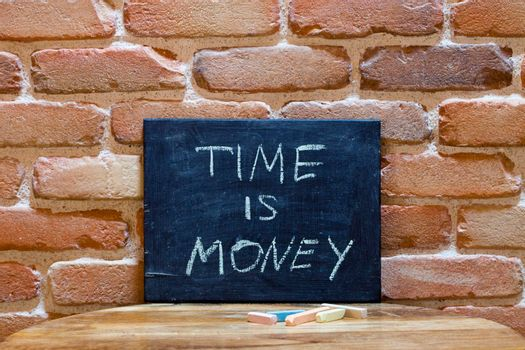 """Black board with the phrase """"Time is Money"""" drown by hand on wooden table on brick wall background. For business presentation."""
