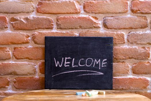 Black board with the word WELCOME drown by hand on wooden table on brick wall background. You are welcome concept.