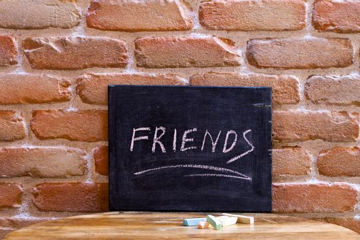Black board with the word FRIENDS drown by hand on wooden table on brick wall background. Friendship concept.