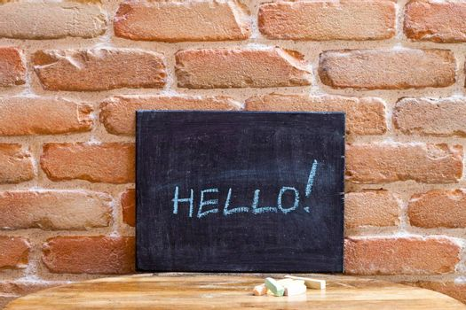 Black board with the word HELLO! drown by hand on wooden table on old brick wall background.