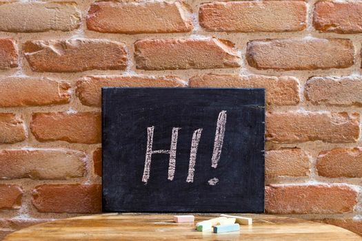 Black board with the word HI! drown by hand on wooden table on old brick wall background.
