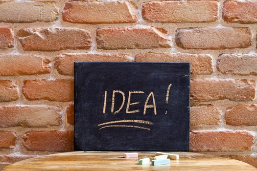 Black board with the word IDEA drown by hand on wooden table on brick wall background. For business presentation.