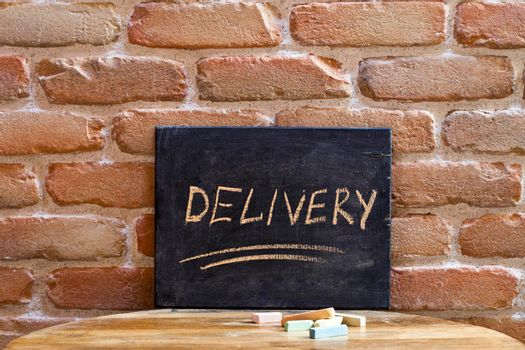 Chalk board with the word DELIVERY drown by hand on wooden table on brick wall background. For business presentation.