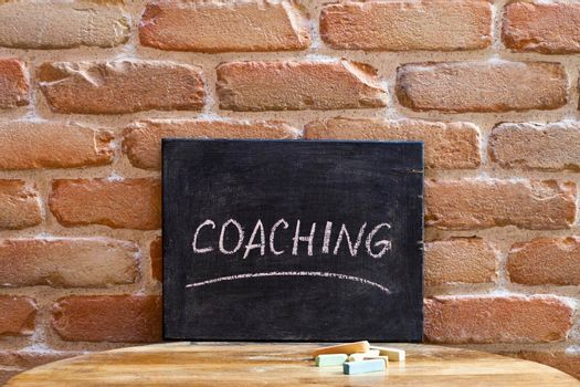 Chalk board with the word COACHING drown by hand on wooden table on brick wall background. For business presentation.