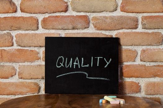Chalk board with the word QUALITY drown by hand on wooden table on brick wall background. For business presentation.