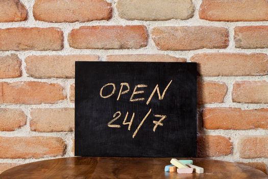 Black chalkboard with the phrase OPEN 24/7 drown by hand on wooden table on brick wall background. Presentation concept.