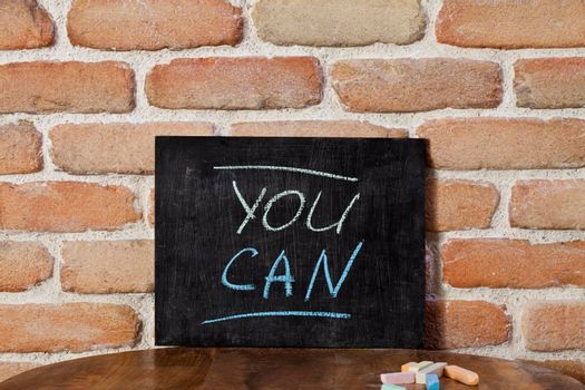 Black board with the phrase YOU CAN drown by hand on wooden table on brick wall background. Presentation concept.