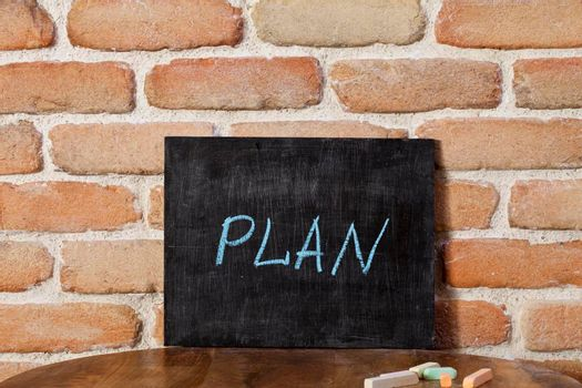 Chalk board with the word PLAN drown by hand on wooden table on brick wall background. For business presentation.