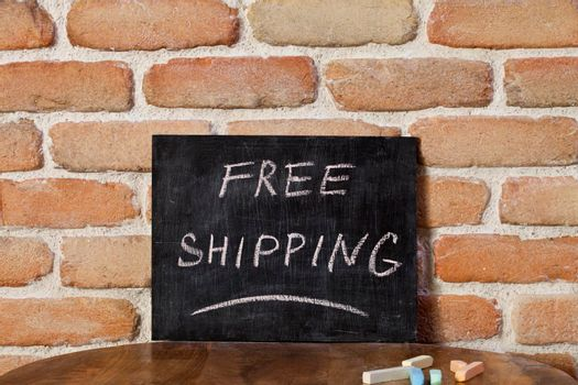 Black chalkboard with the phrase FREE SHIPPING drown by hand on wooden table on brick wall background. For business presentation.