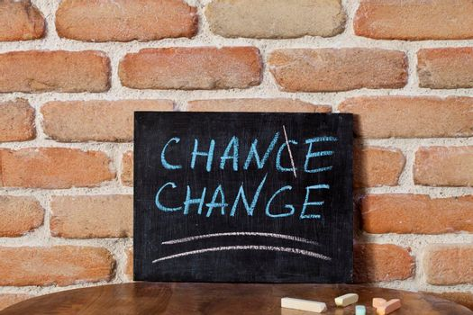 Black board with the phrase CHANCE CHANGE drown by hand on wooden table on brick wall background. For business presentation.