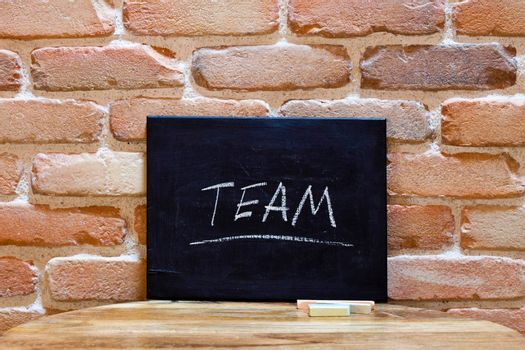 """Blackboard with the word """"Team"""" drown by hand on wooden table on brick wall background. For business presentation."""