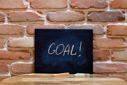 """Blackboard with the word """"Goal"""" drown by hand on wooden table on brick wall background. For business presentation."""