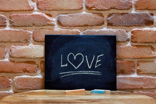 """Black board with the word """"Love"""" drown by hand on wooden table on brick wall background. Love concept."""