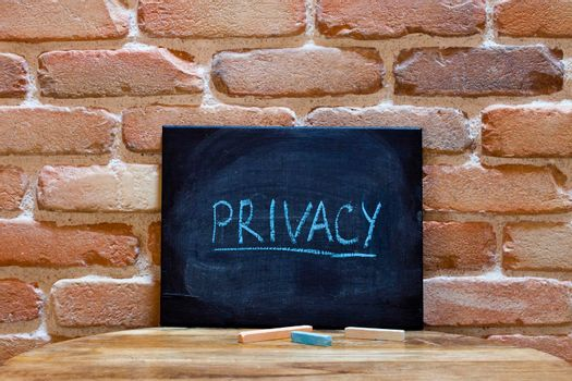 """Black board with the word """"Privacy"""" drown by hand on wooden table on brick wall background. For business presentation."""