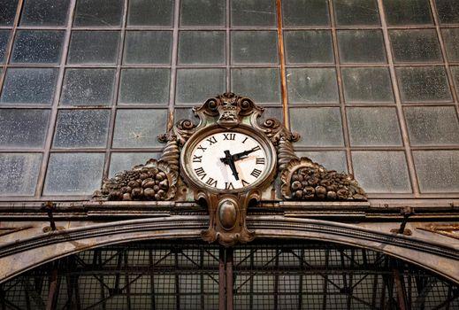 Old clock hanging on ancient market wall. Ancona, Italy.