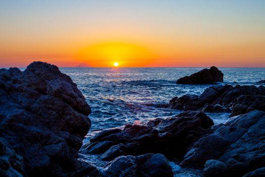 Sunset on the rocky shore. Tyrrhenian Sea sunset in Calabria, Italy.