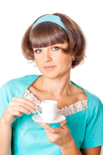 Portrait of young woman in blak dress enjoying a cup of coffee on white background.