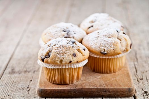 Four homemade fresh muffins with sugar powder and blueberries on cutting board on rustic wooden table background.
