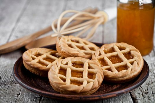Fresh baked tarts with marmalade or apricot jam filling and on ceramic plate and kitchen bakery utensil on on rustic wooden table background.