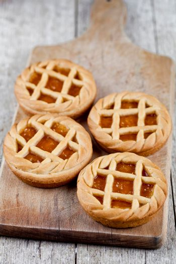 Fresh baked tarts with marmalade or apricot jam filling on cutting board on on rustic wooden table background.