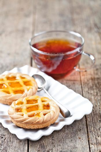 Fresh baked tarts with marmalade or apricot jam filling on white ceramic plate and cup of tea on rustic wooden table background.