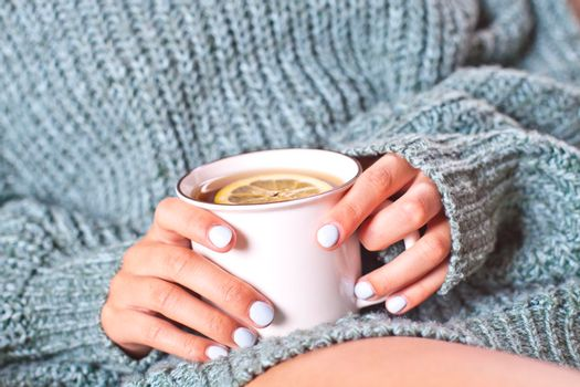 Female hands holding mug of hot tea with lemon in morning. Young woman relaxing tea cup on hand. Good morning tea or have a happy day message concept.