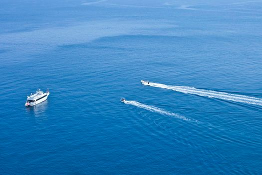 View of boats sailing across the blue clear waters of Adriatic Sea. Tremiti Islands, Italy.