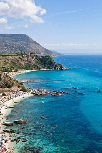Amazing tropical panoramic view of turquoise gulf bay, sandy beach, green mountains and plants, blue sky white clouds background, cliffs platform Cape Capo Vaticano, Calabria, Southern Italy.
