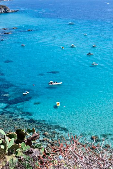 Boats near a rock stone coast. Scenic view of tipycal rocky coastline. Thyrrenian Sea. Cape Capo Vaticano, Calabria, Southern Italy.