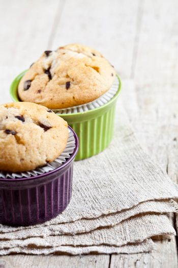 Homemade fresh muffins on ceramic bowls on linen napkin on rustic wooden table background. With copy space.