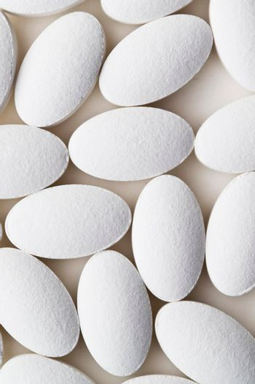 Pile of white drug pills laying on white background