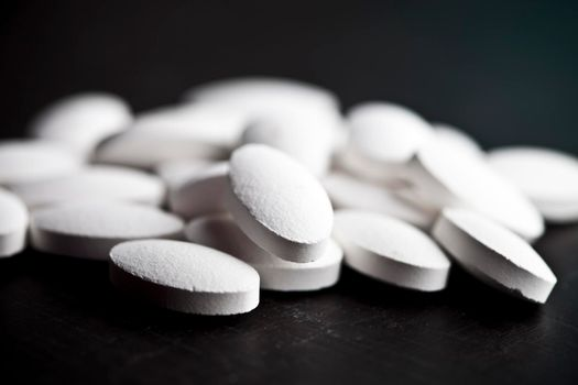 Pile of white drug pills laying on black board background.