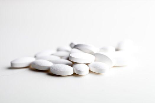 Pile of white drug pills laying on white background.