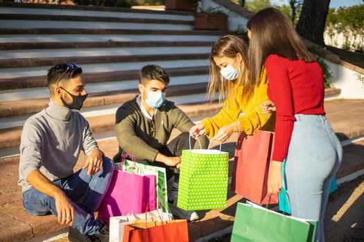 Group of young friends sitting on the steps of the city square wearing protective face masks against covid-19 coronavirus and look into their shopping bags at their newly made purchases