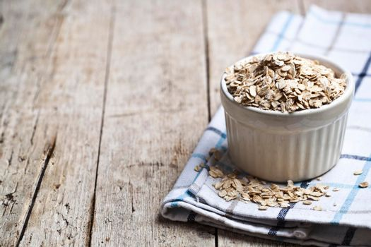 Oat flakes in ceramic bowl on linen napkin, golden wheat ears on rustic wooden background. Healthy lifestyle, healthy eating concept with copy space.