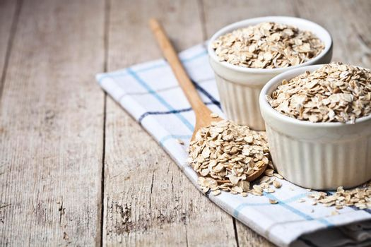 Oat flakes in ceramic bowls and wooden spoon on linen napkin, golden wheat ears on rustic wooden background. Healthy lifestyle, healthy eating concept with copy space.