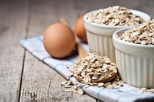 Fresh chicken eggs, oat flakes in ceramic bowl and wooden spoon on rustic wooden table background. Bakery tools with copy space.