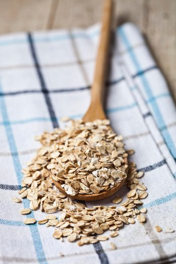 Oat flakes in wooden spoon on linen napkin, golden wheat ears on rustic wooden background. Healthy lifestyle, healthy eating concept.