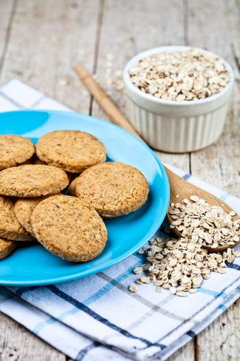 Fresh baked oat cookies on blue ceramic plate on linen napkin and oak flakes on rustic wooden table background.