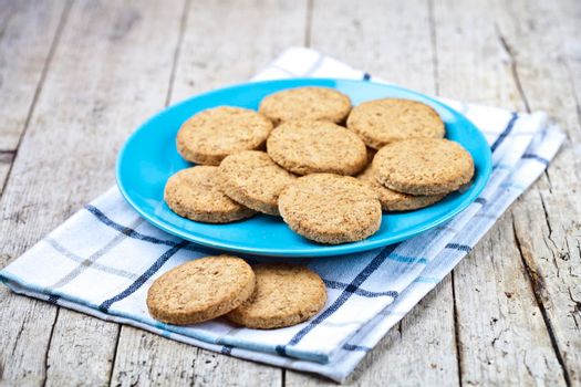 Fresh baked oat cookies on blue ceramic plate on linen napkin on rustic wooden table background.