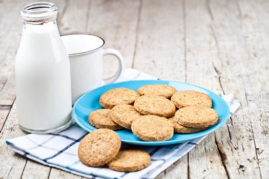 Fresh baked oat cookies on blue ceramic plate on linen napkin, bottle of milk and ceramic cup on rustic wooden table background. With copy space.