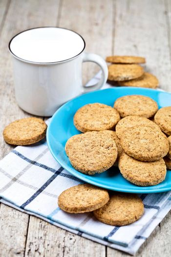 Fresh baked oat cookies on blue ceramic plate on linen napkin and cup of milk on rustic wooden table background.