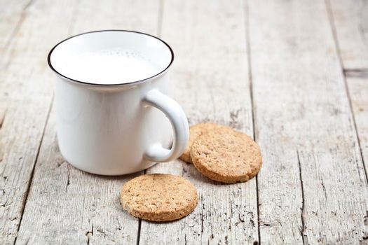 Cup of milk and some fresh baked oat cookies on rustic wooden table background. With copy space.