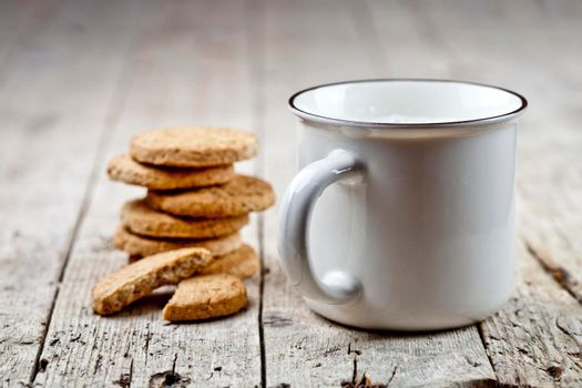 Cup of milk and stack of fresh baked oat cookies on rustic wooden table background. With copy space.