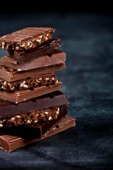 Chocolate bar pieces closeup. Sweet food photo concept.