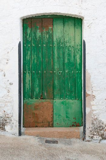 old green painted wooden door in a stone wall in southern in spain