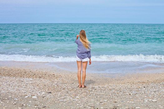 Beautiful girl in sea style on the Adriatic beach. Travel and vacation.