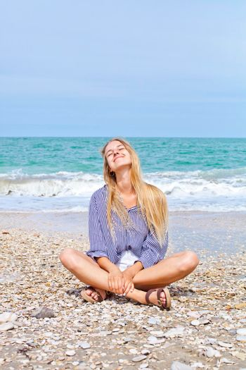 Beautiful happy girl on the Adriatic beach. Travel and vacation. Freedom concept.