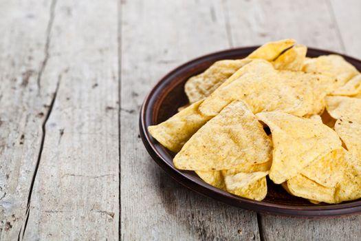 Nachos chips on brown ceramic plate.