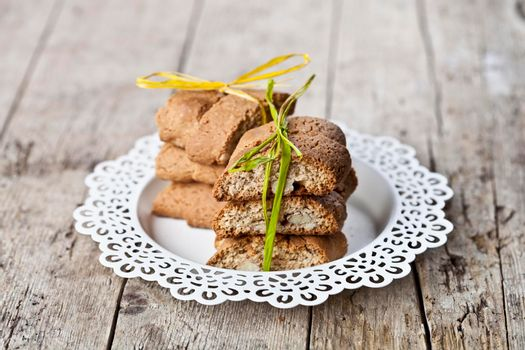 Fresh Italian cookies cantuccini on white plate on ructic wooden table background.
